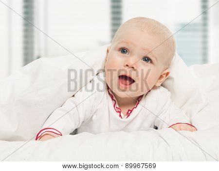Little Girl Baby Laying Under White Blanket