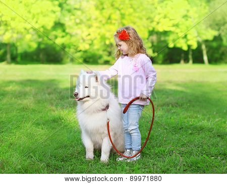 Child With White Samoyed Dog On The Grass In Sunny Summer Day