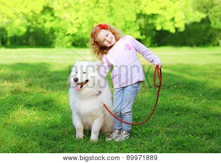 Happy Child With White Samoyed Dog On The Grass In Sunny Summer Day