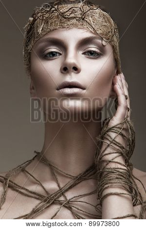 Beautiful girl with a bronze skin, pale makeup and unusual accessories. Art beauty image.