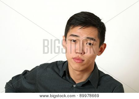 Pleased young Asian man looking at camera.