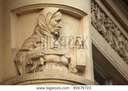 Old woman with a key and a lamp. Art Nouveau building decoration at Bubenecska Street in Prague, Czech Republic.