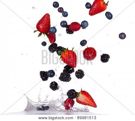Fresh raspberries, strawberries, blackberries and blueberries in water splash isolated on white background