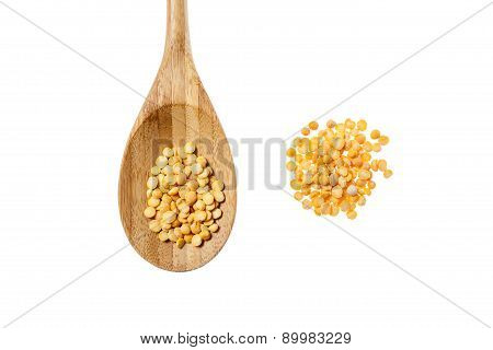Yellow peas grain and spoon on white background.