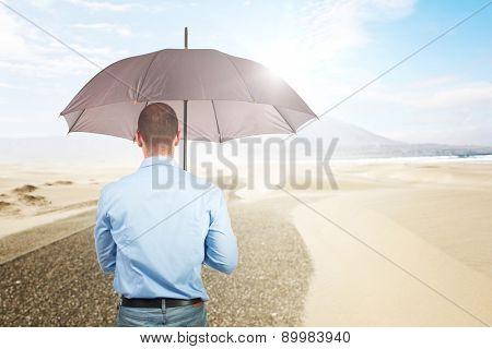 man with umbrella and desert background
