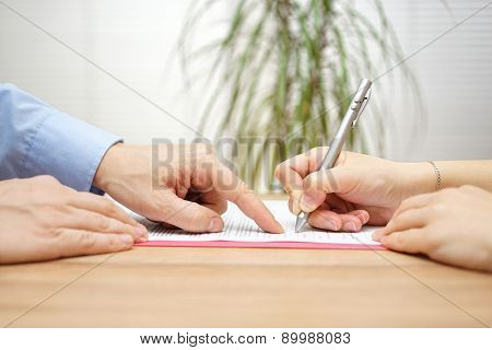 Man Is Pointing A Place Where She Should Sign The Agreement