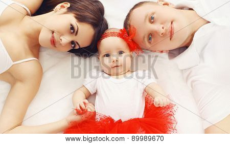 Beautiful Young Family Lying Together On The Bed At Home, Parents And Baby, Top View