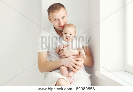 Father And Baby At Home In White Room Sitting Near Window