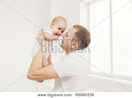 Happy Father Holding On Hands His Baby At Home In White Room