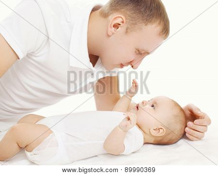 Happy Young Father With His Baby On The Bed At Home