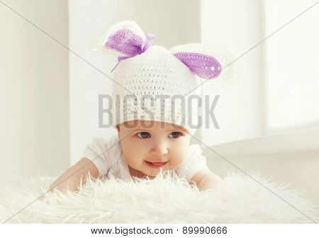Portrait Of Cute Baby In White Knitted Hat With Ears Rabbit At Home