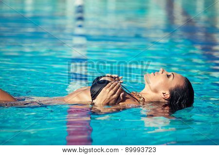Sexy swimmer. A slender sexy lady in bikini balancing on her back in blue water.