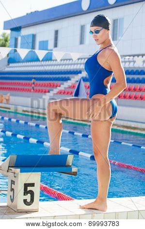 Portrait of a female swimmer, that wearing a swimming cap and goggles and preparing to jump into swi