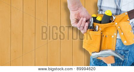 Technician with tool belt around waist against wooden planks