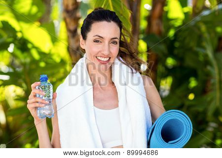 Smiling brunette holding bottle of water and exercise mat on a sunny day
