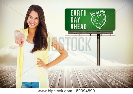 Happy casual woman pointing to camera against wooden planks leading to bright sky