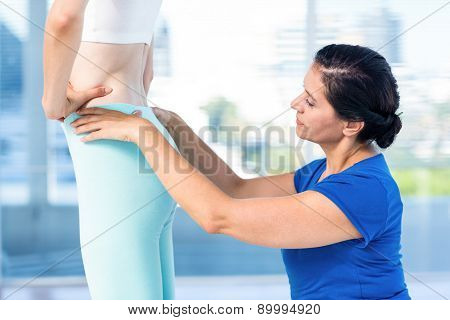 Therapist examining her patients back in exercise room