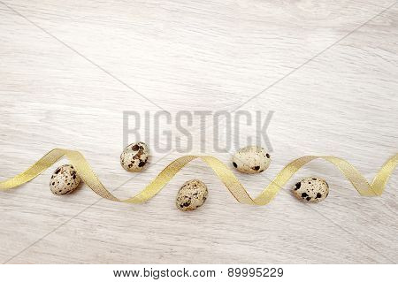 Beautiful Easter Eggs On Wooden Background And Yellow Ribbon