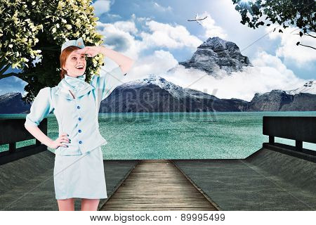 Pretty air hostess looking up against scenic backdrop