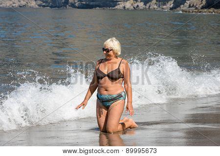 Aged Woman Is Kneeling In Splashing Of Ocean Waves.