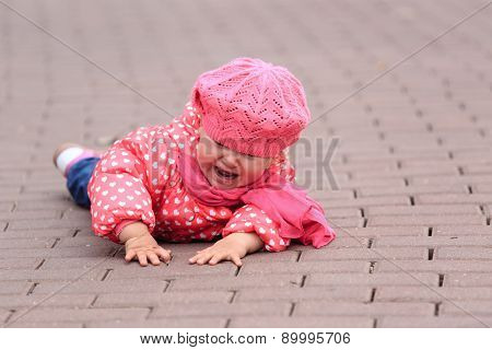 crying little girl fall off on sidewalk