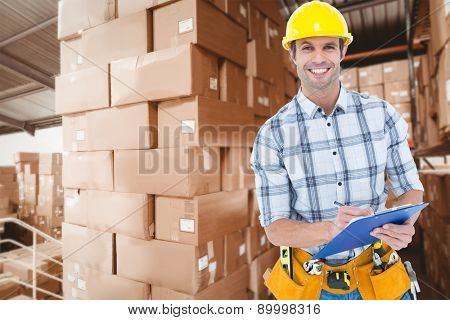 Happy architect writing notes on clip board against shelves with boxes in warehouse