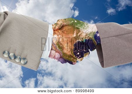 Side view of business peoples hands shaking against bright blue sky with clouds