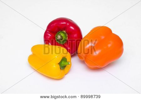 Three whole peppers of different colors