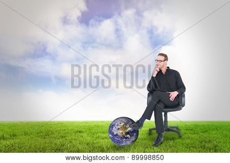 Thoughtful businessman sitting on a swivel chair against green field