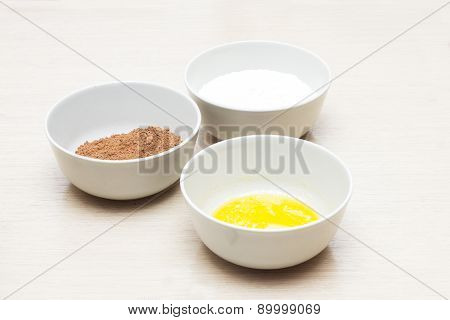 Bowl with home eggs, bowl with cocoa and bowl with milk, product photo