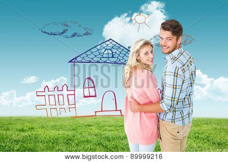 Attractive couple turning and smiling at camera against blue sky over green field