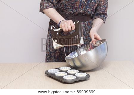 Woman with kitchen mixer whisking dough for cupcakes