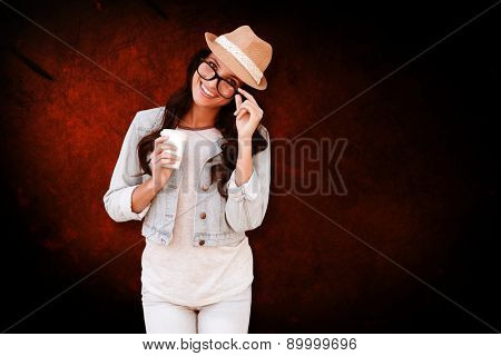 Brunette with disposable cup against dark background
