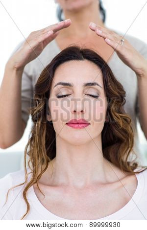Woman getting reiki therapy on white background