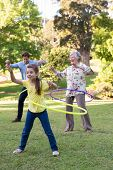 picture of extended family  - Extended family playing with hula hoops on a sunny day - JPG