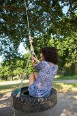 picture of tire swing  - Pretty young woman in tire swing on a summers day - JPG