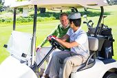 picture of buggy  - Golfing friends driving in their golf buggy on a sunny day at the golf course - JPG