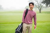 pic of golf bag  - Golfer standing holding his golf bag at the golf course - JPG