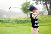 stock photo of take off clothes  - Golfer teeing off at the golf course - JPG