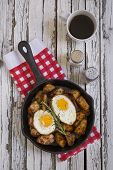 image of baked potato  - Seasoned baked potatoes in a black cast iron frying pan with a sprig of rosemary on a wooden table top with a red and white checkered pattern dish towel salt and pepper shakersa cup of black coffee two fried eggs and a spatula - JPG