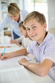stock photo of schoolboys  - Young smiling schoolboy in classroom - JPG
