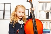 stock photo of hair bow  - Blond girl with curly hair holding the fiddle - JPG