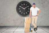 picture of trolley  - Happy delivery man leaning on trolley of boxes against grey room - JPG