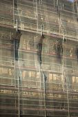 stock photo of scaffolding  - Scaffolding and net on a restoration site - JPG