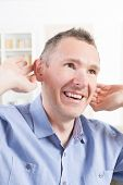 image of deaf  - Man wearing deaf aid in ear attempting to hear something - JPG