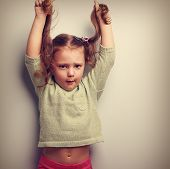 foto of pulling hair  - Active unhappy emotion kid girl pulling her long hair up - JPG