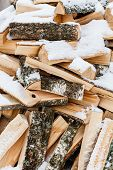 foto of firewood  - Stacked chopped firewood covered by snow - JPG