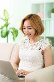 stock photo of korean  - Lovely Korean woman working on laptop at home - JPG
