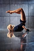 stock photo of upside  - Young woman modern dancer stretching legs upside down - JPG