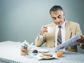 stock photo of nutrients  - Elegant businessman having a nutrient delicious breakfast and reading newspaper - JPG